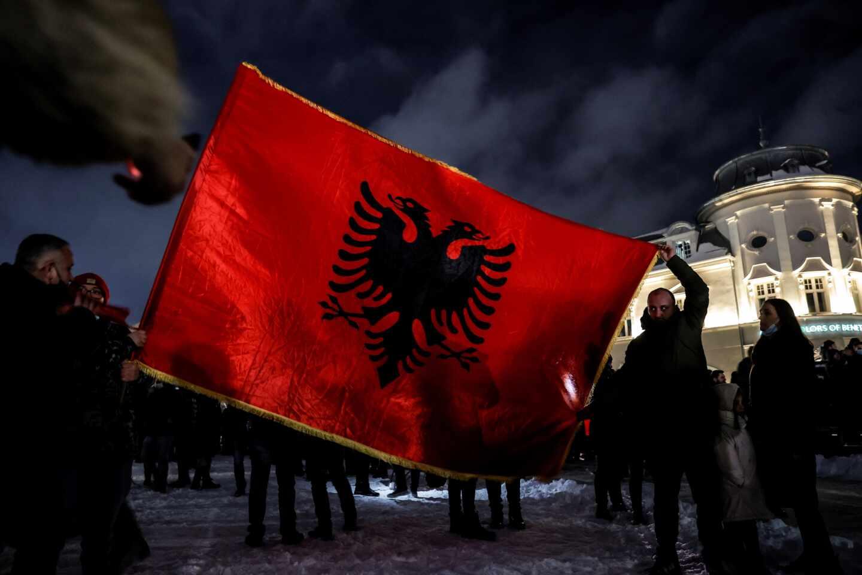Un grupo de seguidores de Vetvendosje celebran la victoria electoral con una gran bandera de Kosovo, en Pristina