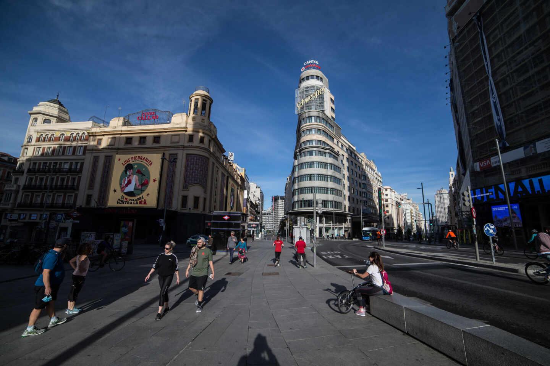 Varias personas pasean por la Gran Vía de Madrid.