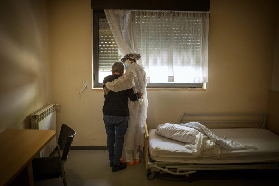 Una enfermera de una residencia de ancianos atiende a un mayor en su dormitorio