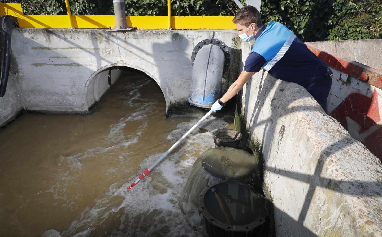 Un técnico toma muestras de aguas residuales.