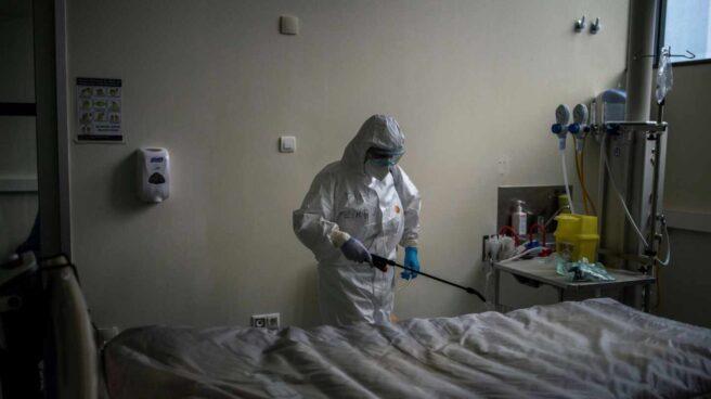 Una trabajadora del servicio de limpieza desinfecta una cama en el interior de la unidad de vigilancia postquirúrgica (REA) del Complejo Universitario de Ourense.