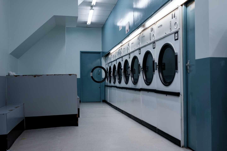 Una imagen del interior de una lavandería con muchas lavadoras
