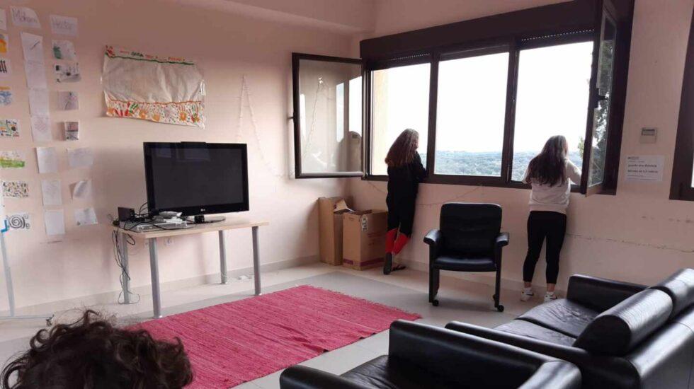 Dos niñas miran por la ventana y otro permanece en el sofá en una de las salas comunes del Centro Gubio para menores con Covid o en cuarentena de la Comunidad de Madrid.