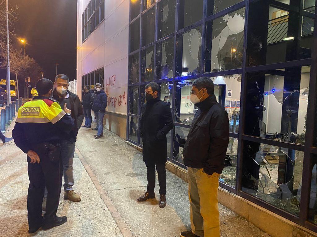 El consejero de Interior de la Generalitat, Miquel Sàmper, habla con un agente de policía frente a las cristaleras destrozadas de la Comisaría de los Mossos en Vic durante las protestas por la detención del rapero Pablo Hasel.