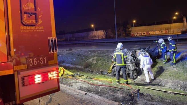 Los bomberos trabajan en la extracción del cadáver del vehículo.