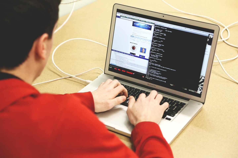 Un hombre escribe código en un ordenador portátil.