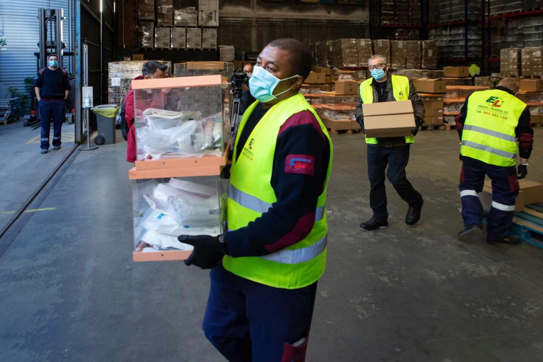 Operarios de los Talleres Municipales del Ayuntamiento de Barcelona trabajan en el almacén donde se guarda el material electoral.