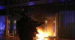 Un mosso, frente a la entrada en llamas de la Bolsa de Barcelona.
