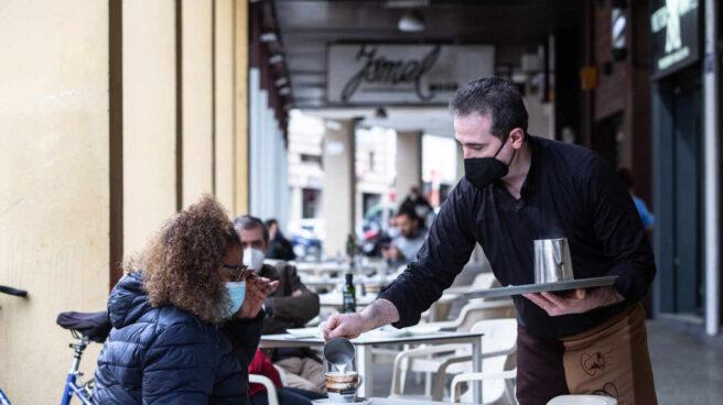 Un camarero sirve un café a una clienta en una cafetería durante el primer día de apertura de bares y restaurantes en Badajoz.