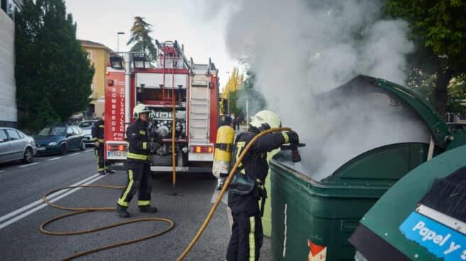 Una dotación de bomberos apaga un contenedor de basura durante una manifestación en el barrio de la Txantrea de Pamplona en apoyo al preso etarra Patxi Ruiz, en mayo de 2020.