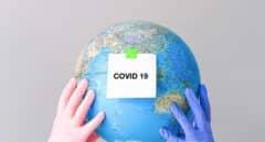"""Dos manos con guantes sujetan un globo terráqueo con una nota en la que se lee """"Covid-19""""."""