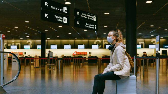 Una chica sentada sobre su maleta espera en un aeropuerto.