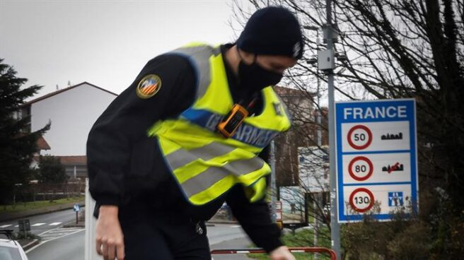 Policía francés con una señal de alto en la frontera de Francia
