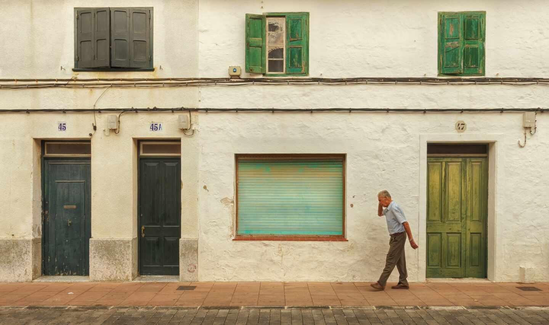 Un hombre de edad avanzada pasea frente a unas casas viejas.