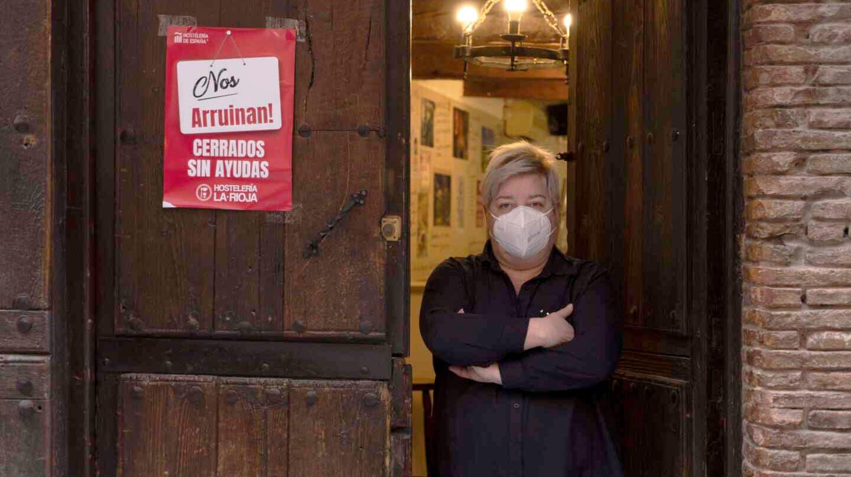 Imagen de una hostelera posa junto a un cartel de protesta por las restricciones en Logroño.