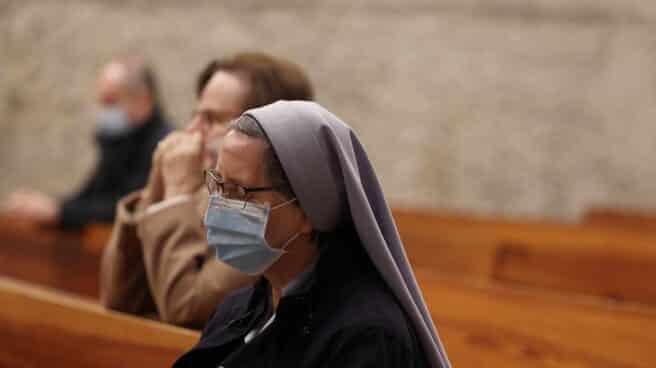 Una monja reza durante la celebración de la Santa Eucaristía en la Parroquia de Santa Elena, en Madrid.