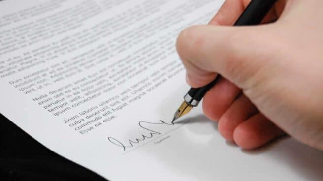 Una foto de archivo de una mano firmando un documento legal similar a la redacción de un testamento.