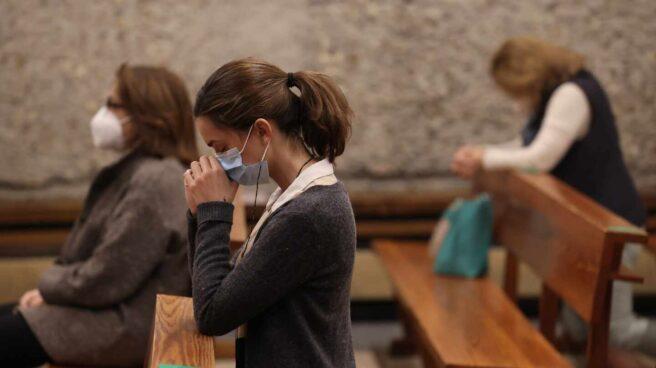 Una mujer reza durante la celebración de una Misa en la parroquia de Santa Elena (Madrid).