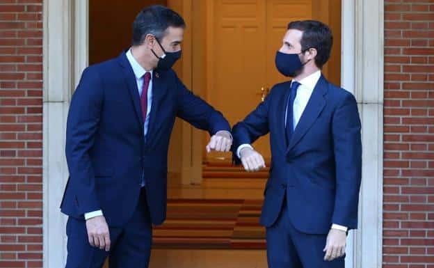 Pedro Sánchez y Pablo Casado, con mascarillas, se saludan chocando el codo en una entrevista que mantuvieron en Moncloa