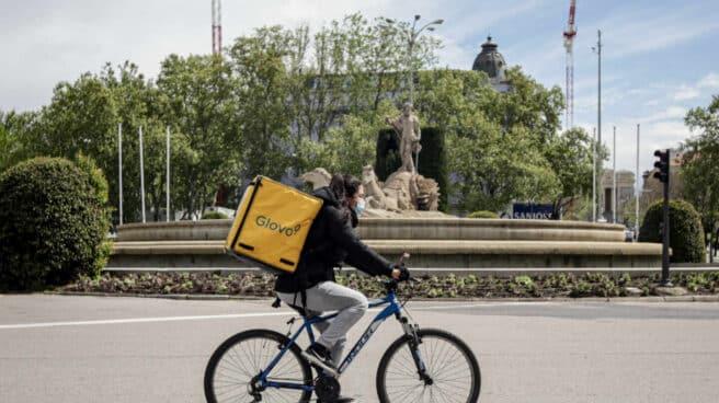 Una repartidora de Glovo en bicicleta por el centro de Madrid.