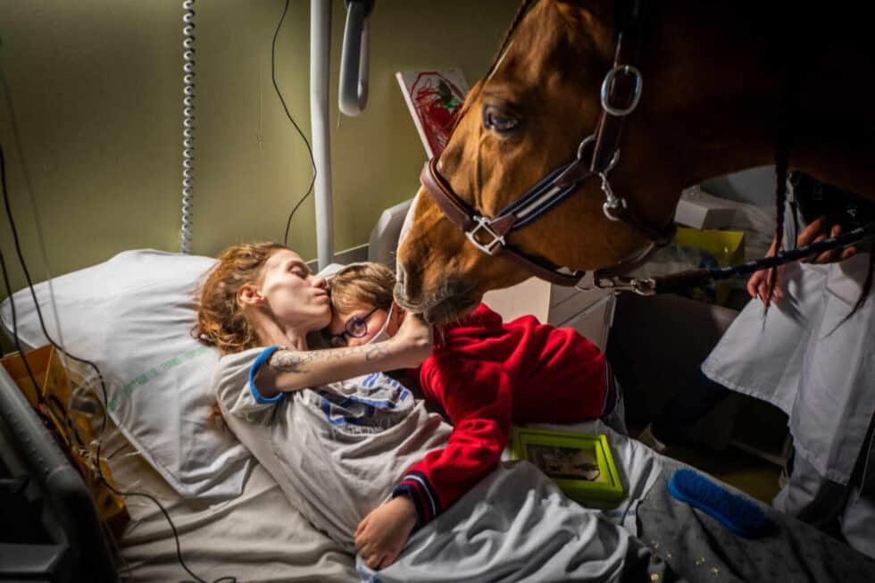 Manon, que tiene cáncer metastásico, abraza a su hijo Ethan en presencia de Peyo, un caballo utilizado en terapia asistida por animales, en la Unidad de Cuidados Paliativos Séléne en el Centro Hospitalario de Calais, en Calais, Francia. el 30 de noviembre.