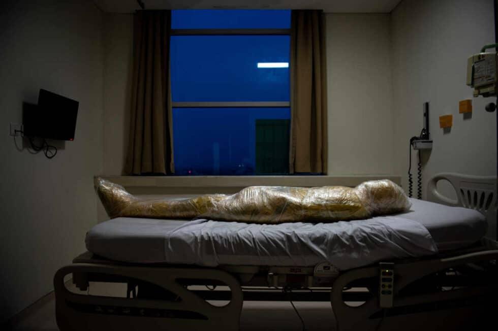 El cuerpo de una víctima del coronavirus, envuelto en bolsas y envoltorios de plástico amarillo para desechos infecciosos