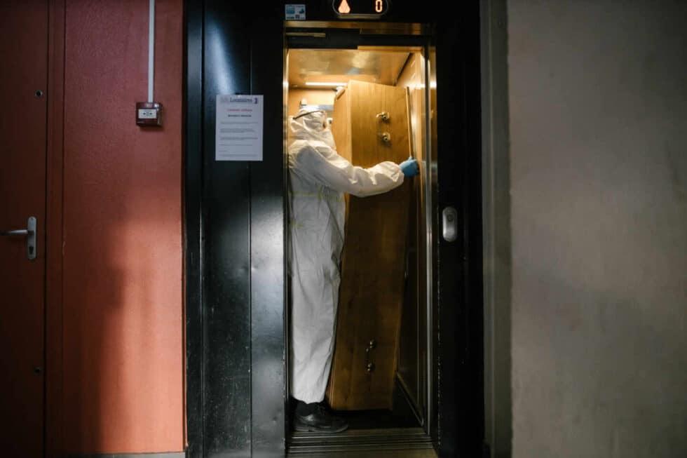 Un hombre porta un féretro en un ascensor.