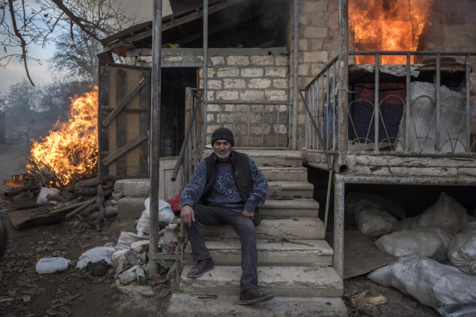 Un residente local de Areg se sienta frente a una casa en llamas en el pueblo de Karegakh, Nagorno-Karabakh. Algunos residentes quemaron sus casas antes de irse. Este conflicto ha pasado bastante desapercibido en un año marcado por la pandemia de Covid-19.