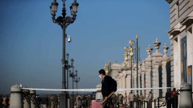Un joven con su maleta pasa ante el Palacio Real de Madrid.