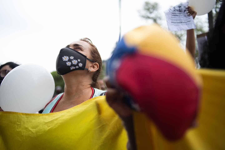 Una mujer manifestándose contra el abuso sexual sosteniendo una pancarta con una mascarilla y mirando al aire