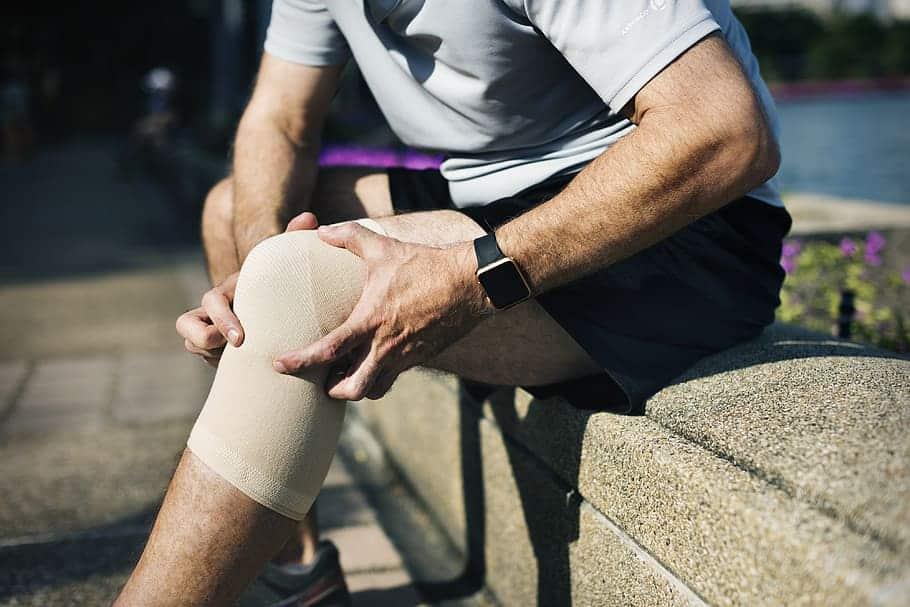 Un hombre con una rodillera sufriendo de dolor en la articulación