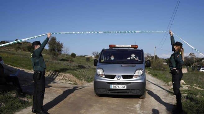 Un furgón de las unidades forenses custodiado por un Guardia Civil