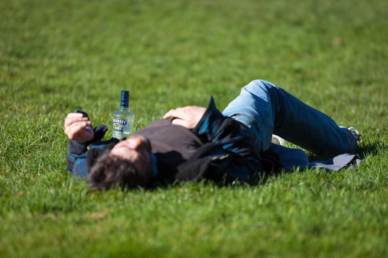 Una persona tumbada en el césped bebiendo alcohol