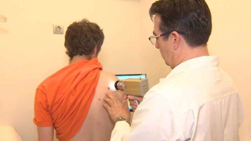Un médico analiza la piel de un paciente.