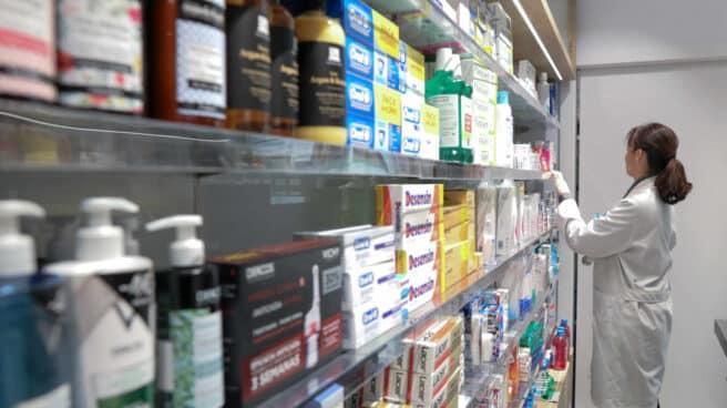 Estante de farmacia con medicamentos, anticonceptivos y antiinflamatorios, y una profesional sanitaria