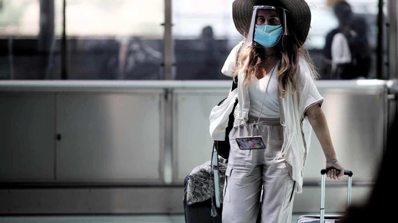 Una pasajera caminando con maleta por un pasillo de la terminar T4 del Aeropuerto Adolfo Suárez Madrid Barajas, en Madrid.