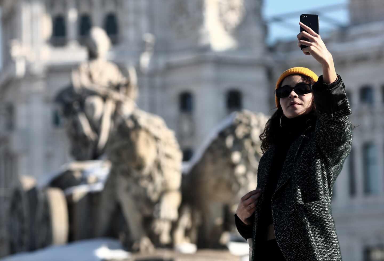 Una mujer se hace un selfie junto a la estatua de Cibeles en Madrid.