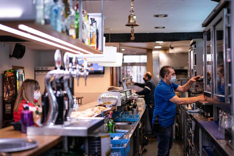 Un trabajador prepara un café en un bar.