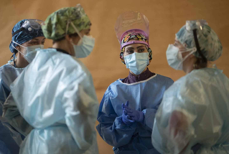 Cuatro trabajadoras sanitarias conversan en un dispositivo de cribado masivo