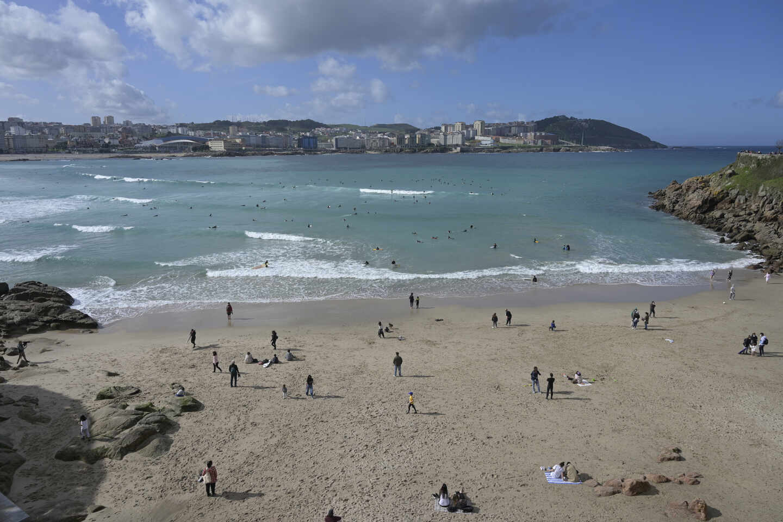 Varias personas disfrutan de la playa del Orzán en A Coruña.