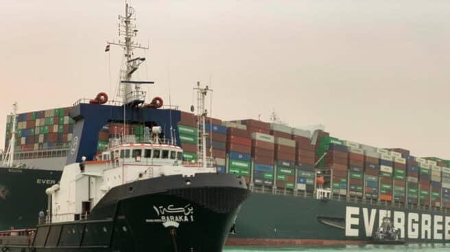 Un remolcador pasa junto al buque portacontenedores llamado Ever Given, operado por Evergreen Marine, encallado en el Canal de Suez.