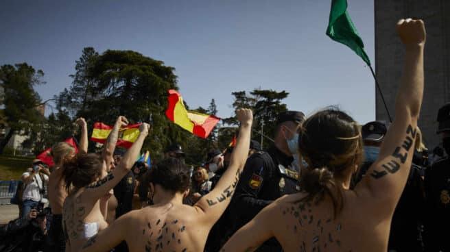 Activistas de Femen con águilas franquistas dibujadas en la espalda durante un acto por el Día de la Victoria, en Madrid