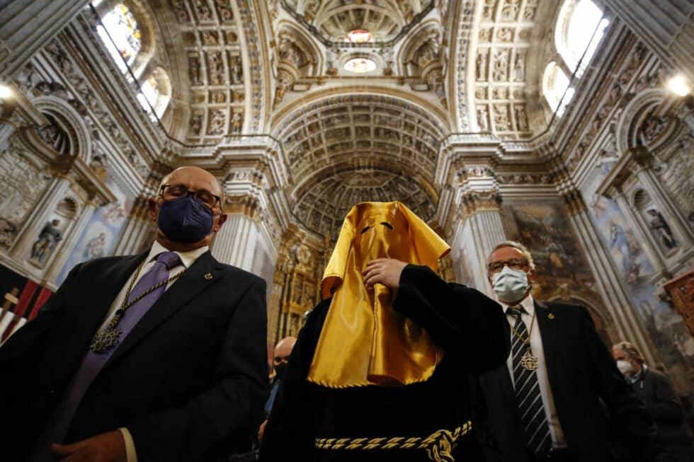 El interior de una iglesia y personas con mascarillas por Semana Santa