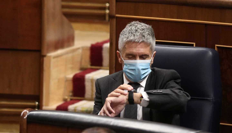 El ministro de Interior, Fernando Grande-Marlaska, consulta el reloj en su escaño del Congreso.
