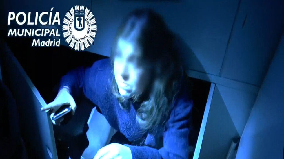 Imagen de una joven saliendo de un armario tras la intervención de la Policía en una fiesta ilegal en La Favorita, un local de Madrid