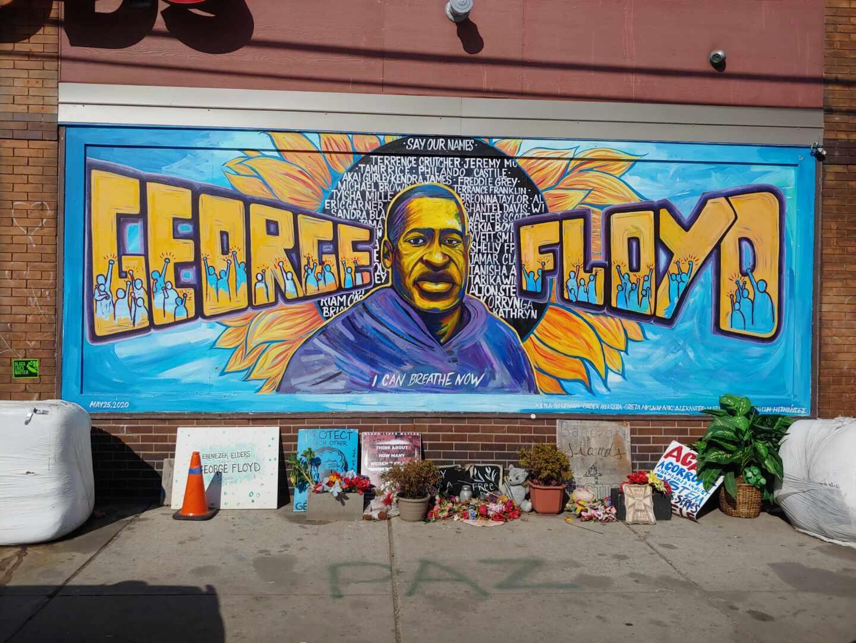 Un gran cartel con la imagen de George Floyd con flores en su recuerdo en Minneapolis