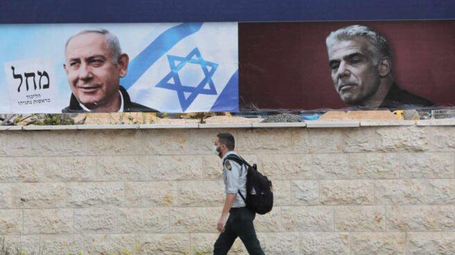 Un israelí pasa cerca de dos carteles electorales, uno de ellos de Netanyahu