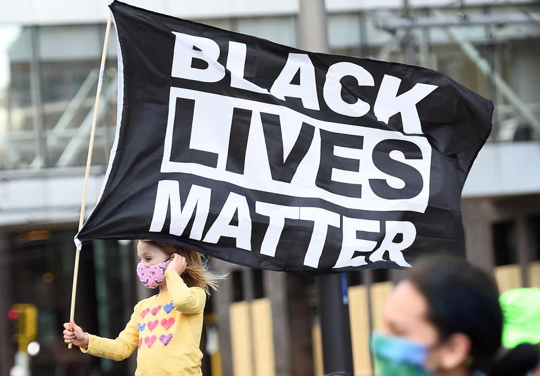 """Una niña porta una bandera que dice 'las vidas de los negros importan"""" en Minneapolis"""
