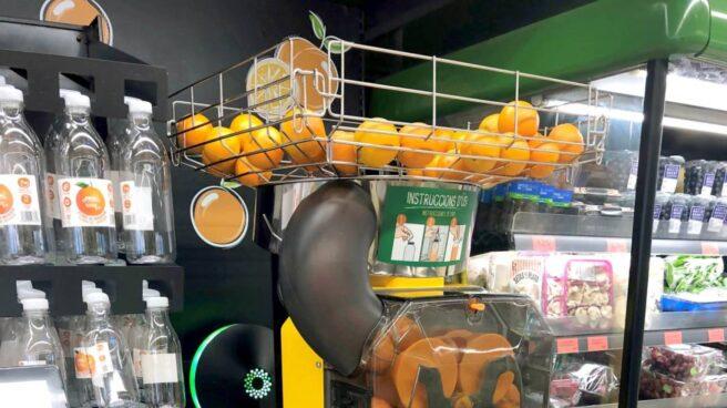 Máquina de zumo de naranja junto a las botellas en Mercadona.