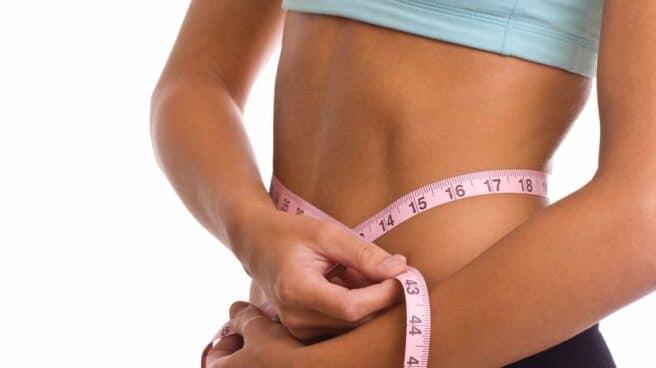 Una mujer con un metro para medir si ha adelgazado o no